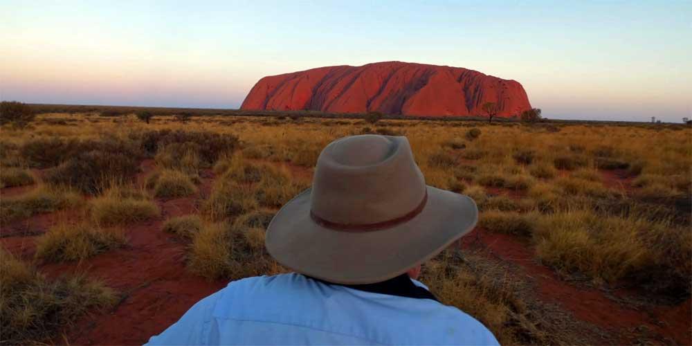 Man mit australischem Akubra vor dem Uluru