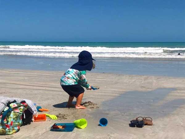 Junge mit Sonnenschutz Cappy am Strand in Australien