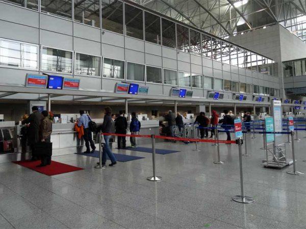 Reisende am CheckIn Schalter am Flughafen